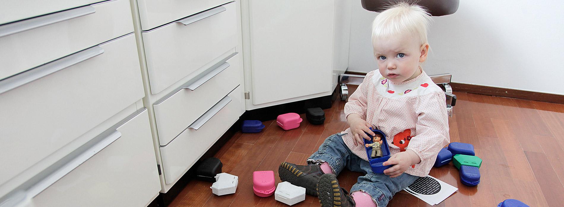 Kind spielt mit Zahnspangen-Dosen